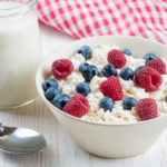cottage cheese with berries in a bowl and jar of milk on white wooden background