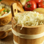 Sauerkraut in a wooden barrel and cabbage soup in the background